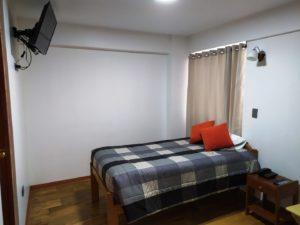 cama simple habitación con tv led de 32